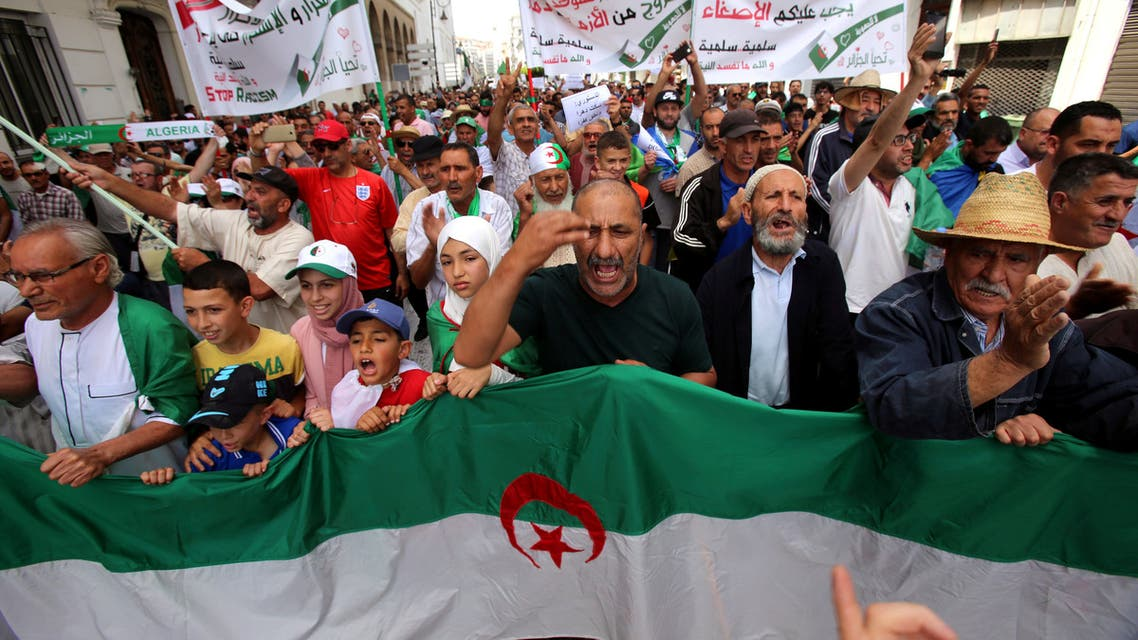 Demonstrators carry a national flag during a protest demanding the removal of the ruling elite in Algiers, Algeria June 7, 2019. REUTERS/Ramzi Boudina
