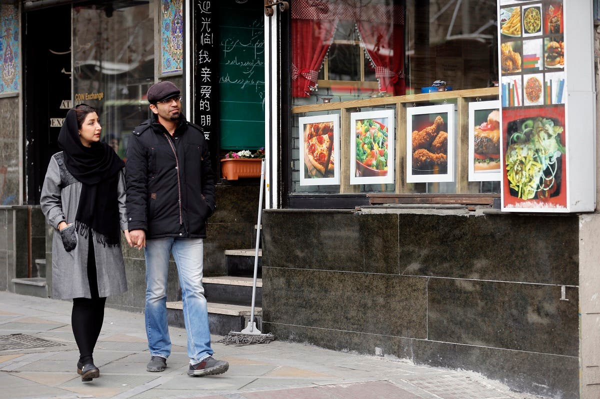 File photo of an Iranian couple walk past a restaurant in the capital Tehran. (AFP)
