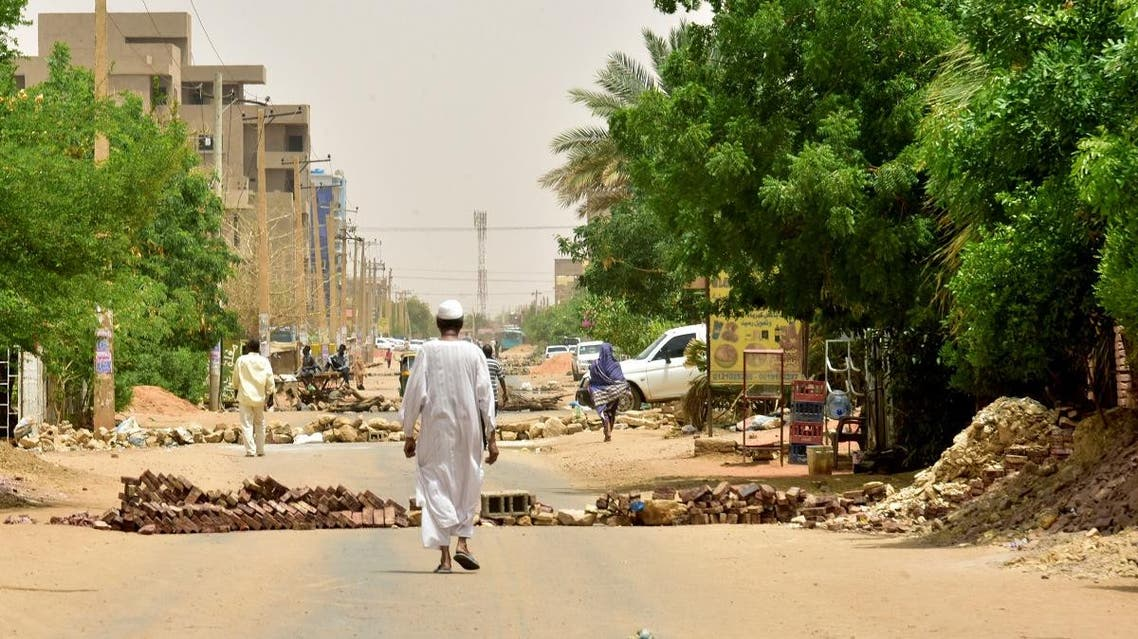 Sudanese residents walk past barricades in Khartoum on June 9, 2019. (AFP)