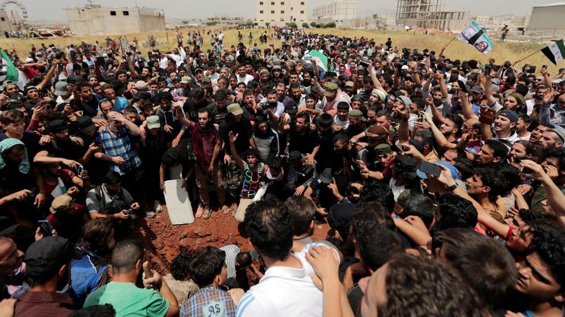 People gesture and chant slogans during the funeral of Abdelbasset al-Sarout. (Reuters)