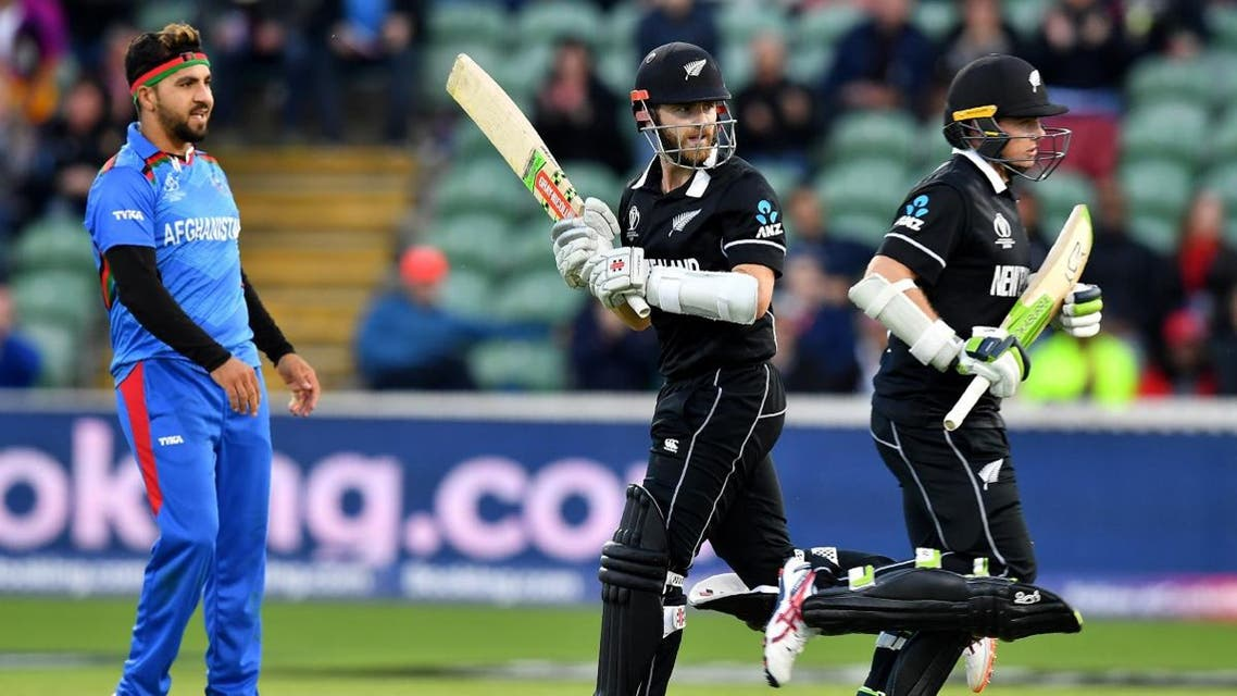 Afghanistan's Aftab Alam looks on as New Zealand's captain Kane Williamson (C) and Tom Latham (R) run between wickets to end the match during the 2019 Cricket World Cup group stage match in Taunton, southwest England, on June 8, 2019. (AFP)