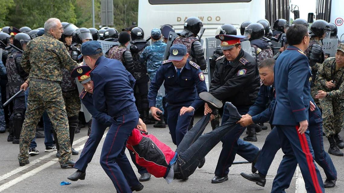 Kazakh police carry a detained demonstrator during an anti-government protest during the presidential elections in Nur-Sultan, the capital city of Kazakhstan, Sunday, June 9, 2019. (AP)