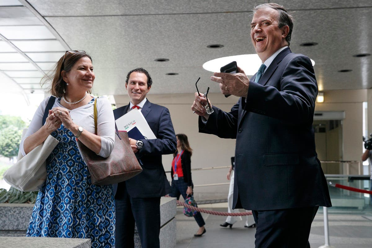 Marcelo Ebrard, Mexico's Secretary of Foreign Affairs, (right), laughs as a reporter asks a question after he spoke to the media while leaving a meeting to talk about tariffs at the State Department, on June 6, 2019, in Washington. (AP)