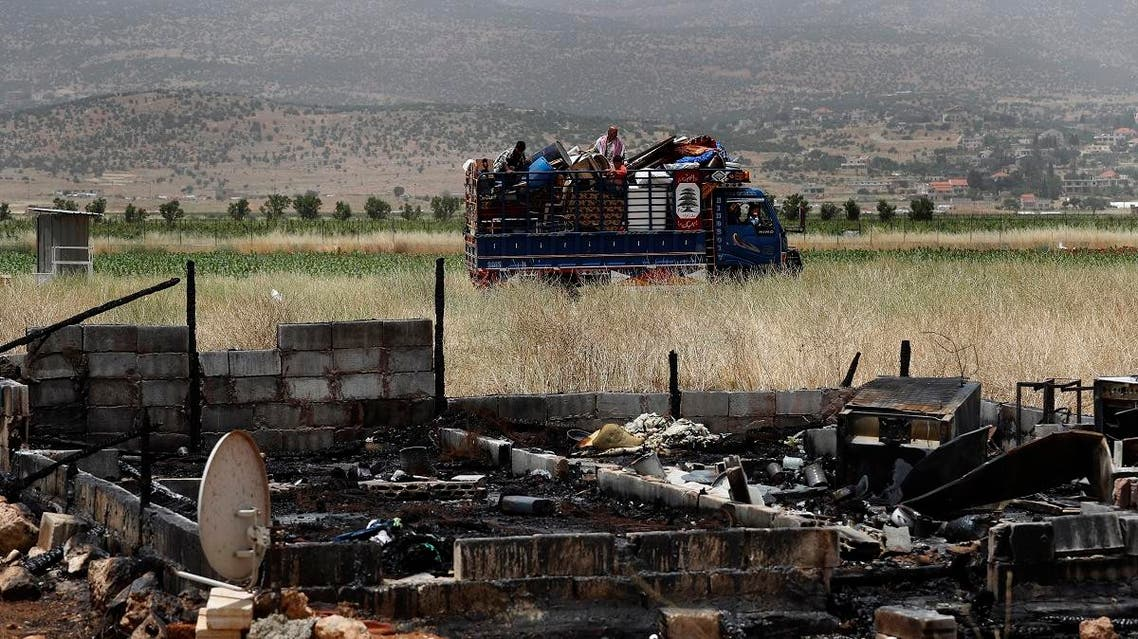 A Syrian family with their belongings ride past a burnt tent in a truck as they evacuate the informal refugee camp in Deir al-Ahmar, east Lebanon, Sunday, June 9, 2019. (AP)