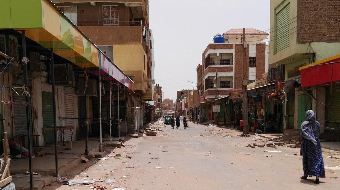 A Sudanese woman walks past closed shops in a commercial street in Khartoum's twin city Omdurman on the first day of a civil disobedience campaign across Sudan on June 9, 2019. (AFP)