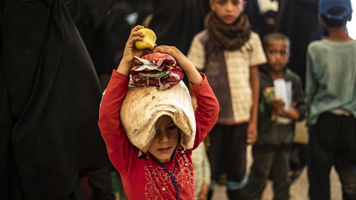 A child carries a bag of bread on his head at the Al-Hol camp in northeastern Syria on June 3, 2019. (AFP)