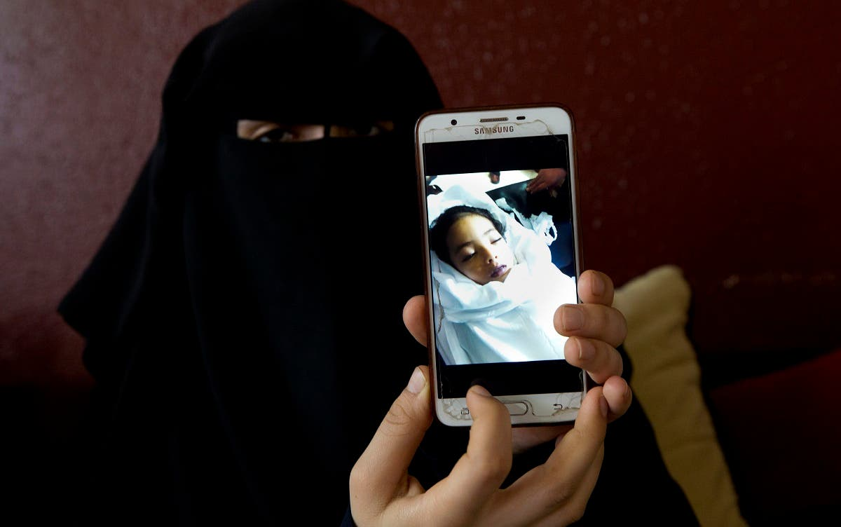 Muna Awad, mother of 5-year-old Aisha al-Loulu, shows a photo of her daughter while in a Jerusalem hospital, at the family home in Bureij refugee camp in central Gaza Strip. (AP)