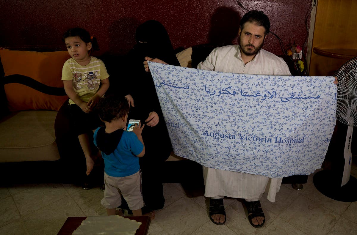 Waseem, father of 5-year-old Aisha a-Lulu, holds the hospital bed sheet his deceased daughter was covered with when she was sent home from a Jerusalem hospital, at the family home in Burij refugee camp, central Gaza Strip. (AFP)