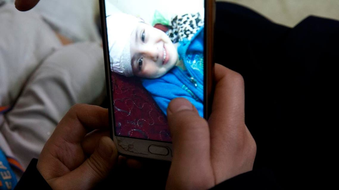 In this May 27, 2019 photo, parents of 5-year-old Aisha a-Lulu, show a mobile photo of their daughter Aisha when she was in a Jerusalem hospital. (AP)