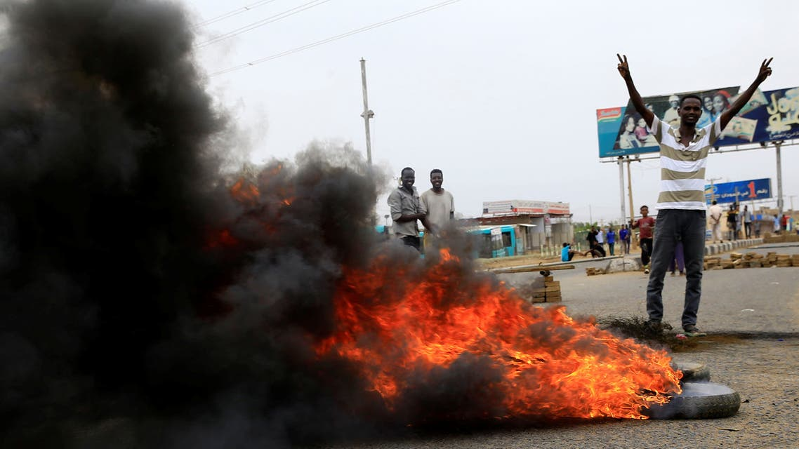 A Sudanese protester gestures near burning tyres used to erect a barricade on a street, demanding that the country's Transitional Military Council handover power to civilians, in Khartoum, Sudan June 4, 2019. REUTERS/Stringer