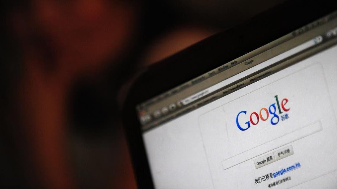 A woman looks on from behind a laptop computer screen displaying the new landing page on google.cn. (AFP)