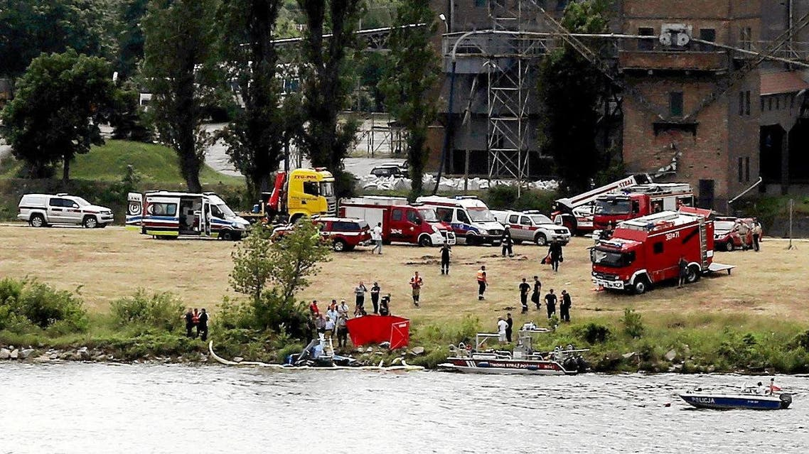 Rescue team work at the scene of the accident after a pilot of a stunt plane plunged into the Vistula River during the Air Picnic in Plock, Poland, on June 15, 2019. (Reuters)
