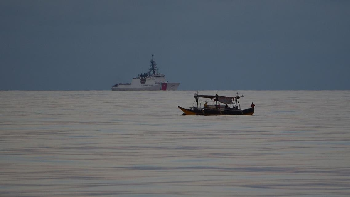 File photo of Filipino fishermen aboard their boat sailing past US coastguard ship Bertholf during a joint exercise between Philippine and US coastguards joint near Scarborough shoal in the South China Sea. (File photo: AFP)