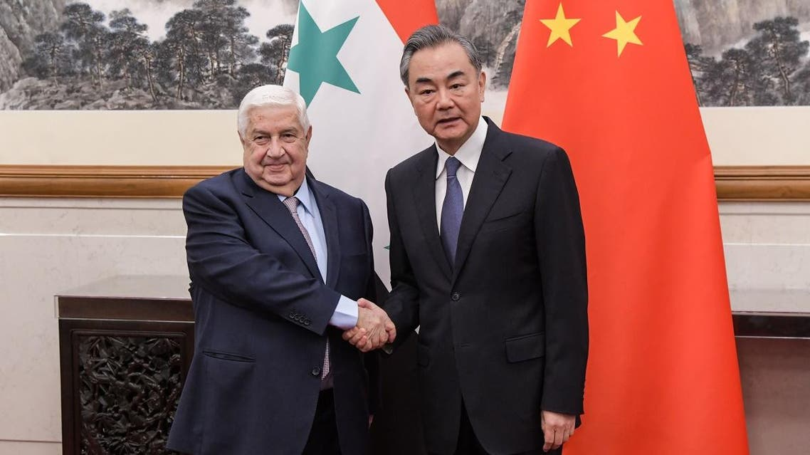 Syrian Foreign Minister Walid Muallem (L) poses for a picture with Chinese Foreign Minister Wang Yi during a meeting at Diaoyutai state guesthouse in Beijing on June 18, 2019. (AFP)