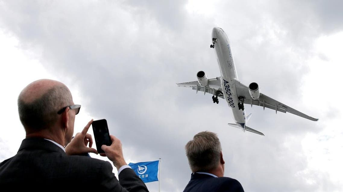 A visitor takes a picture of an Airbus A350-1000 as it performs during the 53rd International Paris Air Show at Le Bourget Airport near Paris, France on June 19, 2019. (Reuters)