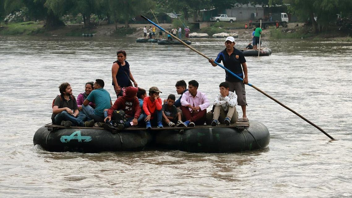Locals and Central American migrants use a makeshift raft across the Suchiate river from Tecun Uman in Guatemala, to Ciudad Hidalgo in Chiapas State, Mexico. (AFP)