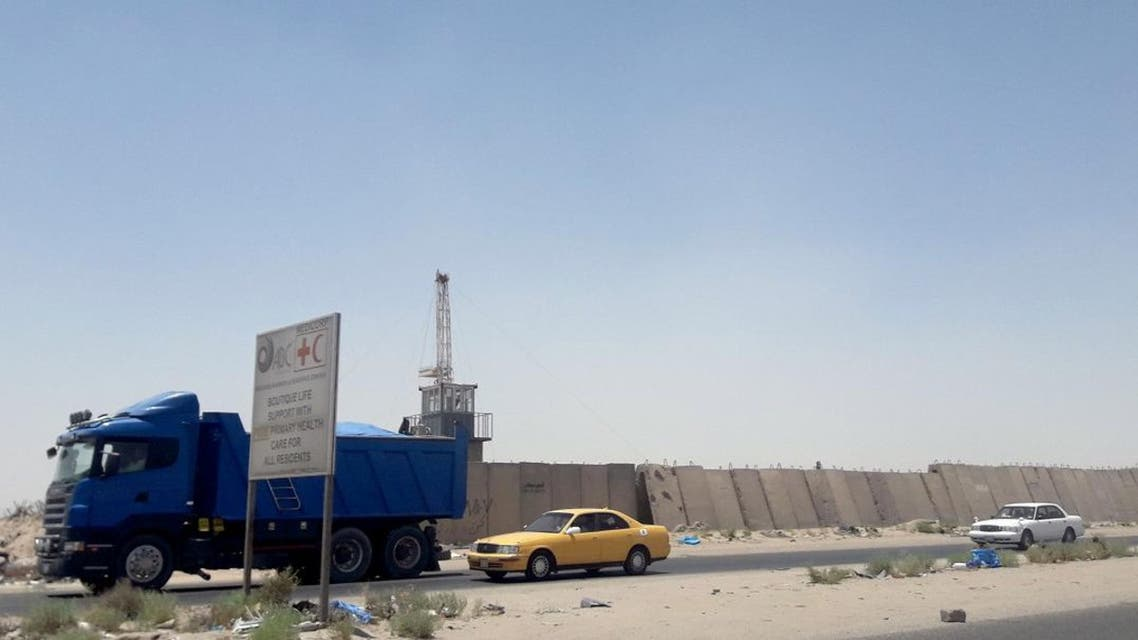 Vehicles drive past next to a security barrier of Zubair oilfield after a rocket landed at a residential and operations headquarters of several oil companies, at Burjesia area in Basra. (Reuters)