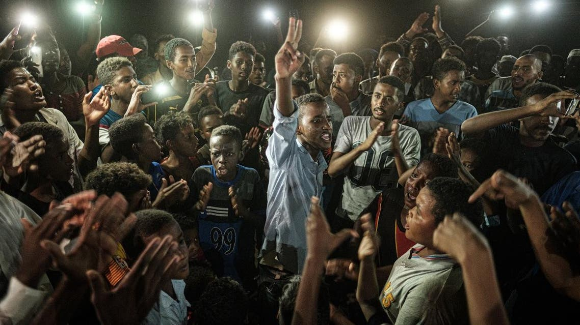 People chant slogans as a young man recites a poem, illuminated by mobile phones, before the opposition's direct dialogue with people in Khartoum on June 19, 2019. (AFP)