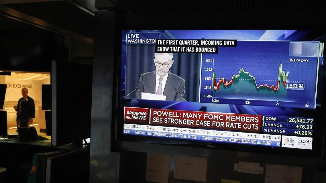 A trader walks on the floor of the New York Stock Exchange as a television displays Federal Reserve Chairman Jerome Powell holding a news conference in New York. (Reuters)