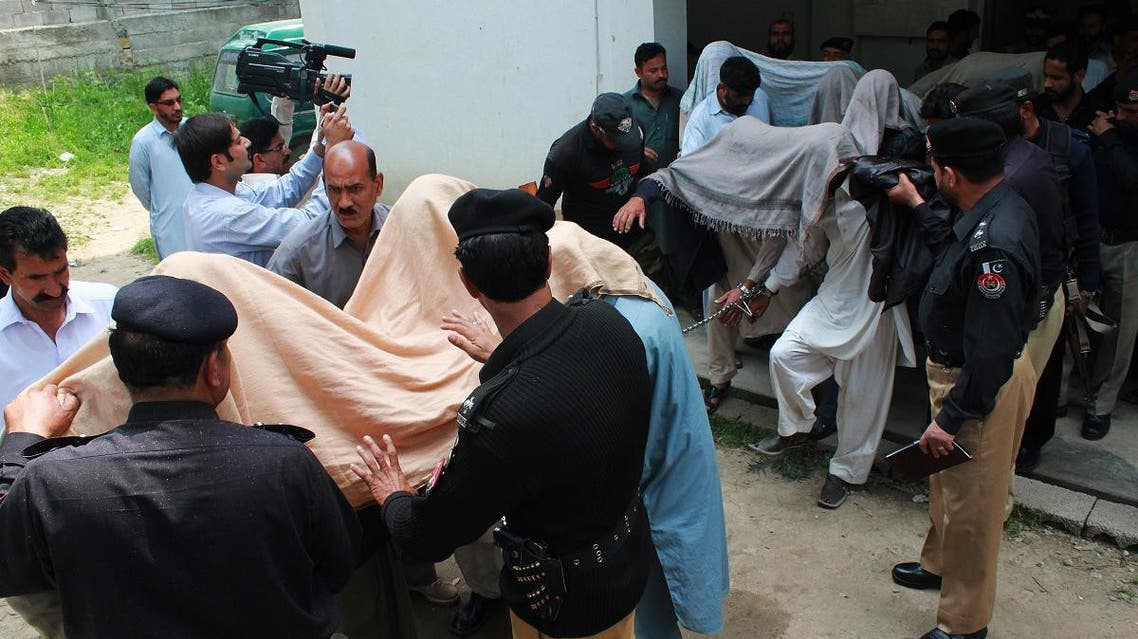 Pakistani police escort suspects accused of killing and setting fire to a woman as they arrive at a court in Abbottabad. (AFP)