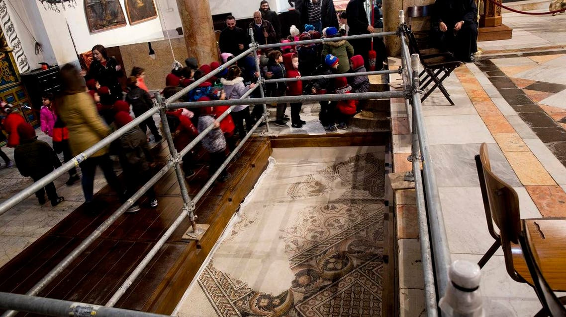 visitors walk by a renovated part of a mosaic inside the Church of the Nativity, built atop the site where Christians believe Jesus Christ was born, in the West Bank City of Bethlehem. (AFP)