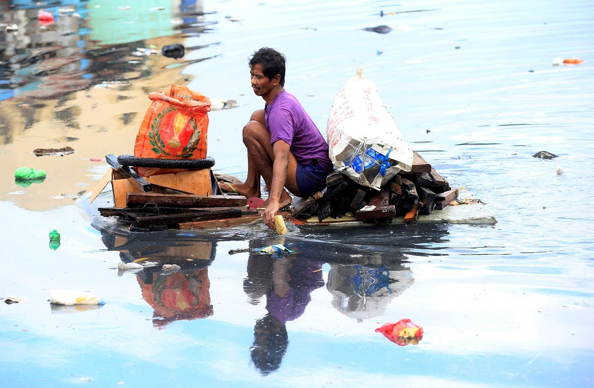 Man uses an improvised banca to collect plastic materials in a polluted river in Manila. (Reuters)