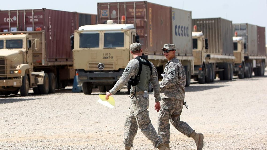 US soldiers walk past army trucks during a logistical operation to clear equipment and heavy machinery from the Balad military base, north of Baghdad. (File photo: AFP)