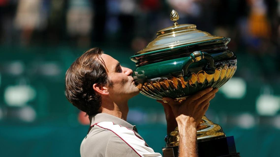 Switzerland's Roger Federer celebrates winning the final against Belgium's David Goffin with the trophy. (Reuters)