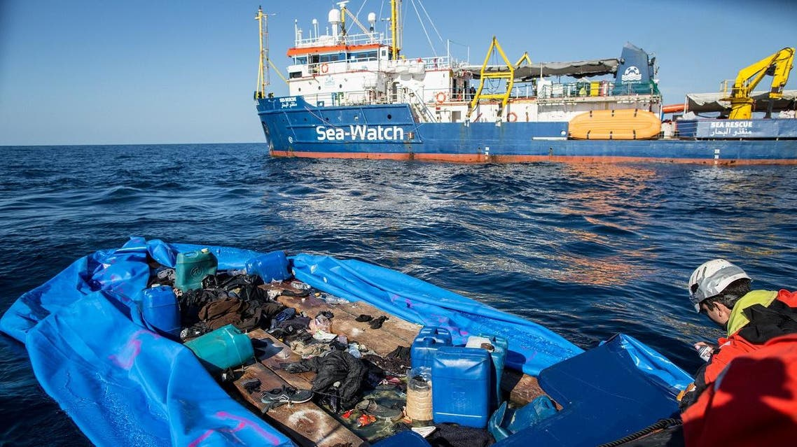 A Sea Watch 3 crew member marks with spray paint a rubber boat that the NGO destroyed after rescuing 47 migrants that were onboard, during a rescue operation by the Dutch-flagged vessel (Rear) off Libya's coasts on January 19, 2019. (AFP)