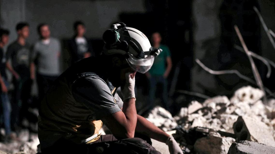 A member of the Syrian Civil Defence reacts as others clear debris while searching for bodies or survivors in a collapsed building following a reported government air strike in the village of Saraqib in Syria's northwestern Idlib province. (AFP)