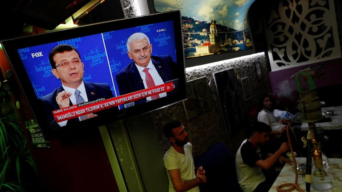 People watch a televised debate between Istanbul's mayoral candidates Imamoglu of CHP and Yildirim of AKP at a cafe in central Istanbul. (Reuters)