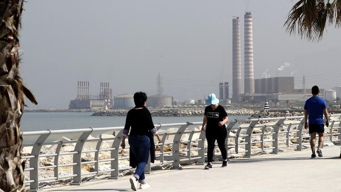 People walk on the seaside promenade with Lebanon's Zouk Mosbeh power plant, north of the capital Beirut seen on April 9, 2019. (AFP)