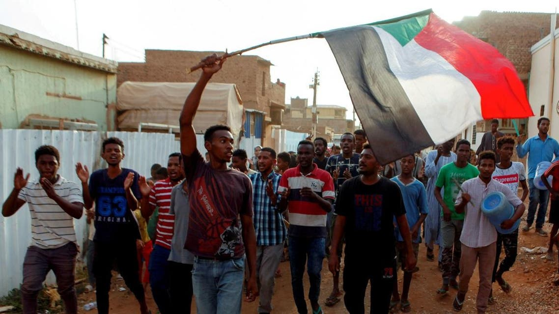 Sudanese protesters chant slogans and wave their national flag as they demonstrate against the ruling military council, in Khartoum. (File photo: Reuters)