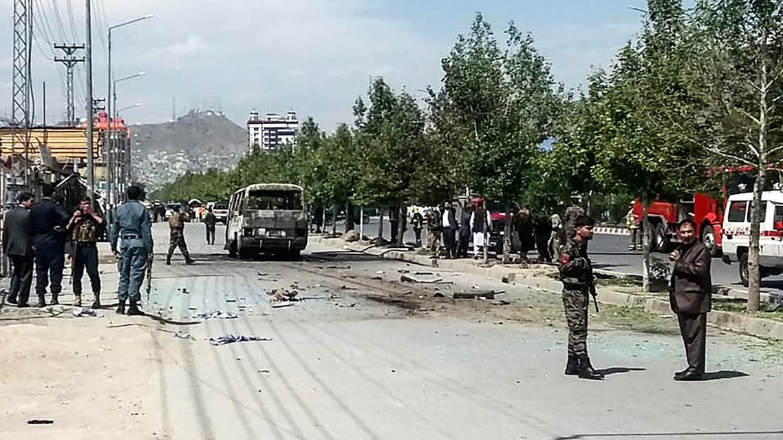 Afghan security personnel stand near a damaged bus carrying workers from a government watchdog agency that was targeted by a bomb blast in Kabul on June 3, 2019. (AFP)