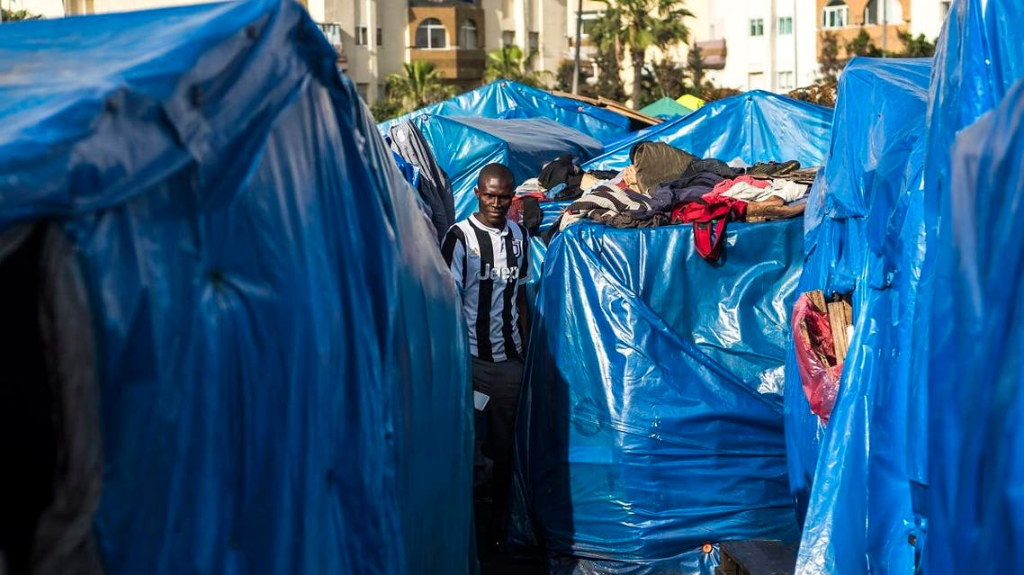 A sub-Saharan migrant walks between make-shift tents in the Oulad Ziane migrant camp in Casablanca on March 27, 2019. (AFP)