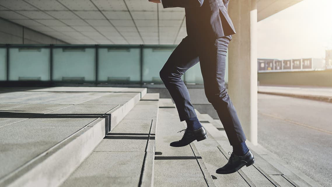 Man wearing suit runs up the stairs - Stock image