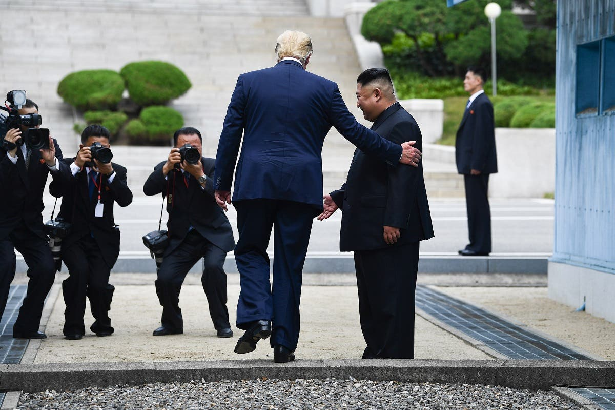 US President Donald Trump steps into the northern side of the Military Demarcation Line that divides North and South Korea, as North Korea's leader Kim Jong Un looks on, on June 30, 2019. (AFP)