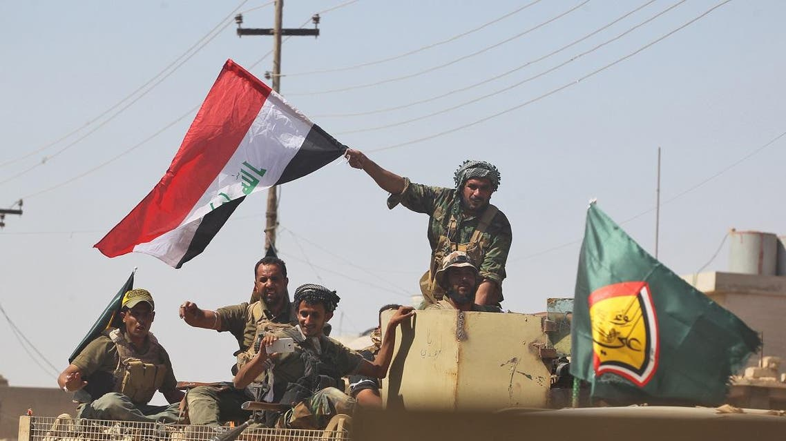 A fighter of Hashed Al-Shaabi (Popular Mobilization militias) waves an Iraqi flag as others use a cell phone to take a selfie from the turret of an armored vehicle during the advance in the town of Tal Afar, west of Mosul. (File photo: AFP)