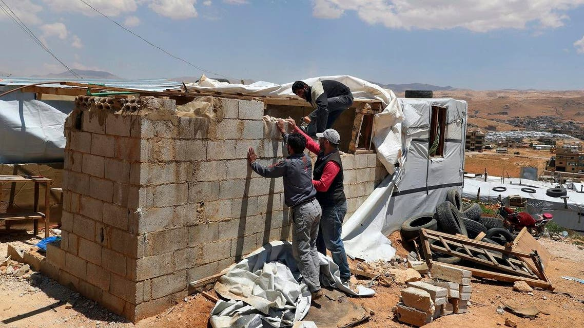 Syrian refugees demolish a concrete wall built inside their tent at a refugee camp in the eastern Lebanese border town of Arsal, Lebanon. (File photo: AP)