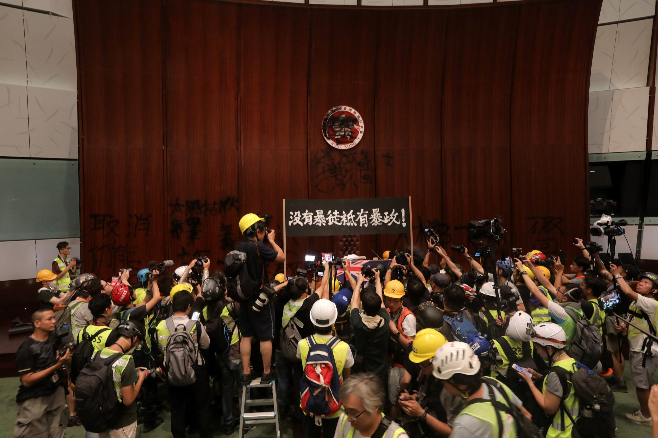 Protesters hold up a sign after they broke into the parliament chamber of the government headquarters in Hong Kong on the 22nd anniversary of the city's handover from Britain to China. (AFP)