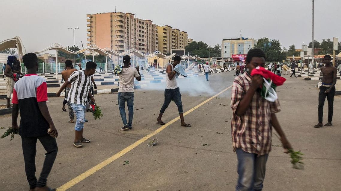 Sudanese protesters cover their faces against tear gas fumes during clashes with security forces in the capital Khartoum on June 30, 2019. (AFP)