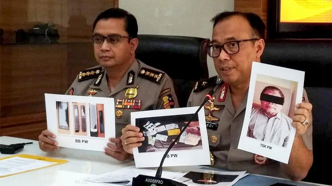 Indonesian police personnel show photographs of leader Para Wijayanto and various seized items, at a press conference in Jakarta on July 1, 2019. (AFP)