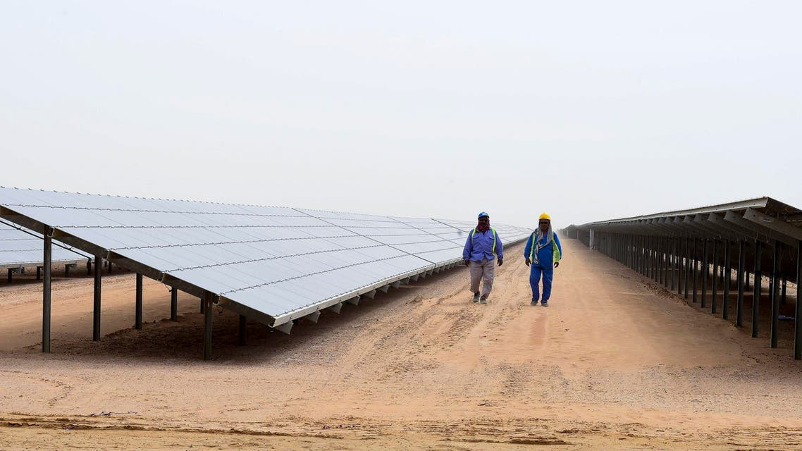Employees walk past solar panels at the Mohammed bin Rashid Al-Maktoum Solar Park on March 20, 2017, in Dubai. Dubai completed a solar plant big enough to power 50,000 homes as part of a plan to generate three-quarters of its energy from renewables by 2050. (AFP)