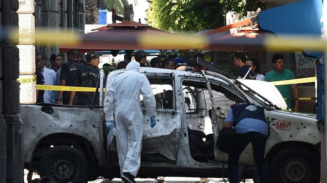 Body parts lie next to a shrapnel riddled vehicle as Tunisian forensic work at the site of attack in the Tunisian capital's main avenue Habib Bourguiba on June 27, 2019. (AFP)