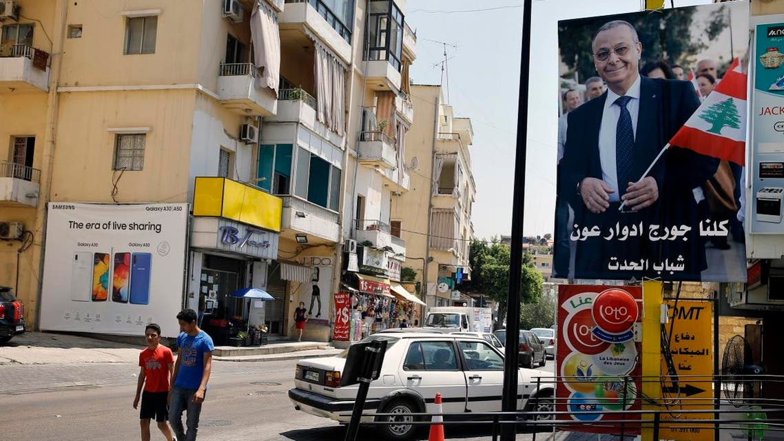 """In this Monday, June 24, 2019 photo, a poster shows George Aoun, head of the municipality of the village of Hadat, with Arabic that reads """"We are all George Edward Aoun. Hadat youth,"""" in the Christian village of Hadat. (AP)"""