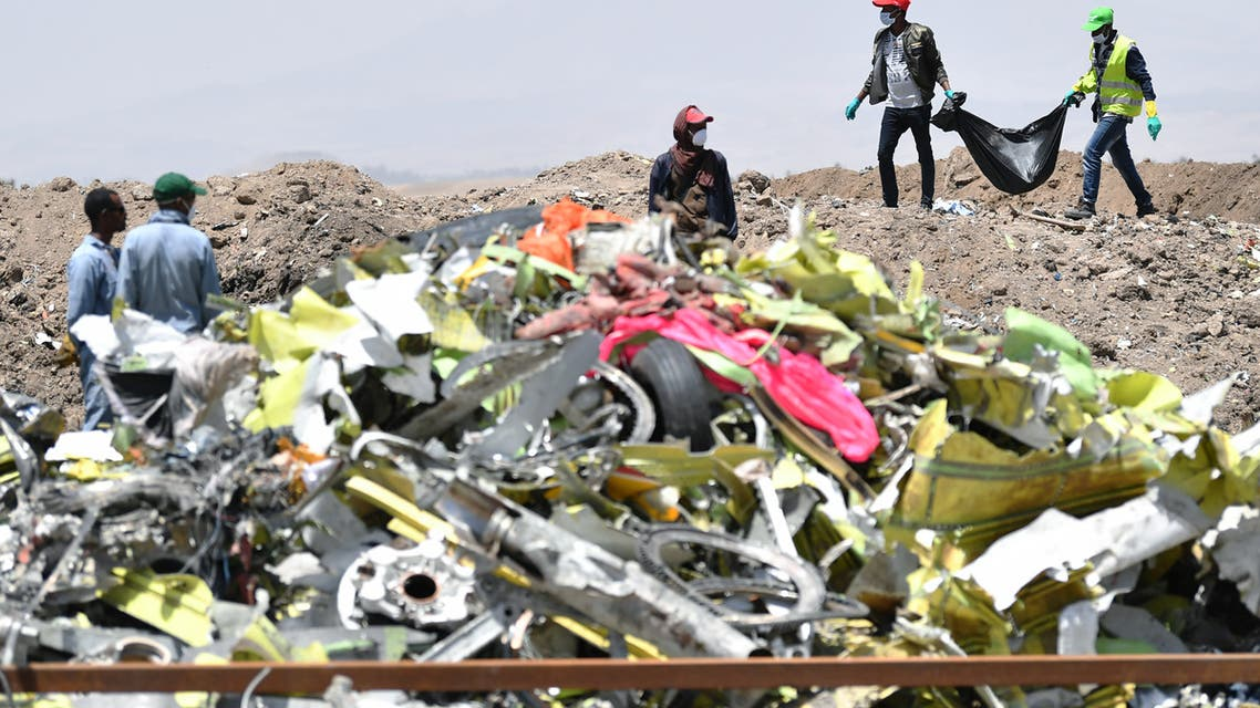 A crew working with an investigative team to clear the site after the Sunday crash of the Ethiopian Airlines operated Boeing 737 MAX aircraft, carry debris at Hama Quntushele village in the Oromia region, on March 13, 2019.
