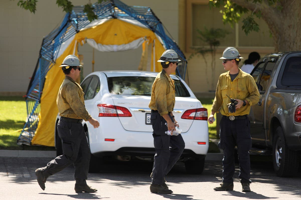 Wildland firefighters pass by hospital equipment being set up outside the Ridgecrest Regional Hospital after a powerful earthquake struck Southern California in the city of Ridgecrest, California, US, on July 4, 2019. (Reuters)
