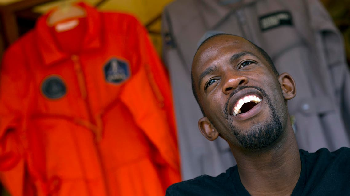Mandla Maseko speaks to a journalist in front of two hanged NASA spacesuits on January 9, 2014, in Mabopane, north of Pretoria. (AFP)