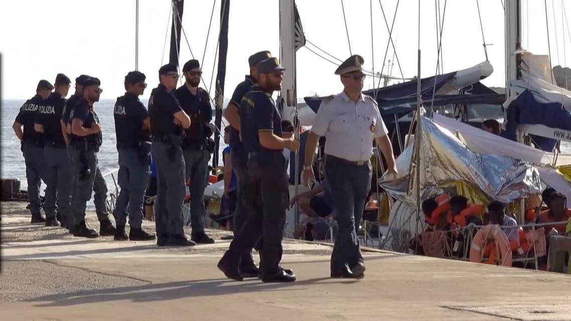 A still image from a video footage shows police officers guarding a migrant rescue boat, which docked at the port of Lampedusa in defiance of a ban on entering Italian waters. (Reuters)