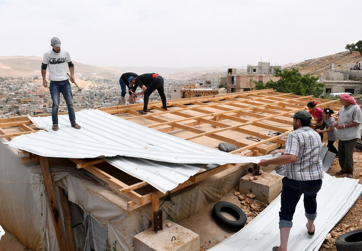 Syrian refugees remove a corrugated metal as they dismantle their shelters at the Lebanese border town of Arsal, Lebanon June 9, 2019. (Reuters)